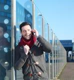 Glücklicher Mann, der draußen am Handy lacht Lizenzfreies Stockfoto