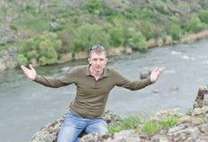 Glücklicher Mann, der ein doppeltes V-Zeichen auf eine Bergkuppe gibt Stockbild