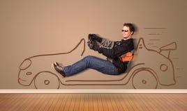 Glücklicher Mann, der ein Hand gezeichnetes Auto auf der Wand fährt Lizenzfreie Stockfotografie