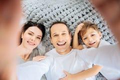 Glücklicher Mann, der ein selfie seiner Familie auf Bett nimmt Lizenzfreie Stockbilder