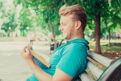 Glücklicher Mann, der eine lustige Geschichte des Buches in einem Park am sonnigen Tag des Sommers liest Lizenzfreie Stockfotografie