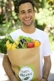 Glücklicher Mann, der eine Tasche des biologischen Lebensmittels trägt. Stockbild