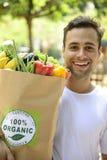 Glücklicher Mann, der eine Tasche des biologischen Lebensmittels trägt. Stockfotografie