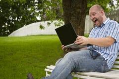 Glücklicher Mann, der in einem Park arbeitet Stockfotografie