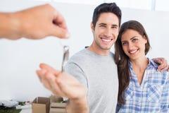 Glücklicher Mann, der einen Hausschlüssel gegeben wird Stockfotografie