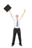 Glücklicher Mann, der einen Koffer hält und Glück mit Erhöhung gestikuliert Lizenzfreie Stockfotos