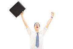 Glücklicher Mann, der einen Koffer hält und Glück mit Erhöhung gestikuliert Lizenzfreies Stockbild