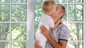 Glücklicher Mann, der entzückenden Sohn in der Backe küsst stock video footage