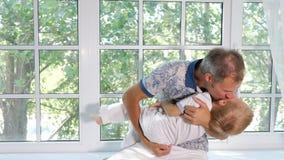 Glücklicher Mann, der entzückenden Sohn in der Backe küsst stock video
