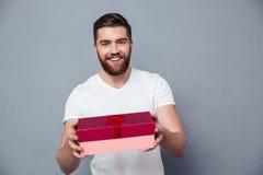 Glücklicher Mann, der Geschenkbox auf Kamera gibt Stockfotografie