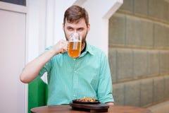 Glücklicher Mann, der helles Bier trinkt und deutsche Würste in der Bar schmeckt stockbild