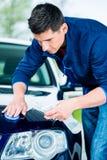 Glücklicher Mann, der Kamera beim Einwachsen eines blauen Autos betrachtet Stockfotografie
