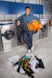 Glücklicher Mann, der leeren Korb mit schmutziger Kleidung hält Lizenzfreie Stockfotos