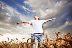 Glücklicher Mann, der mit den geöffneten Armen auf einem Weizenfeld steht Lizenzfreie Stockbilder