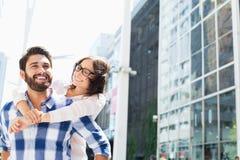 Glücklicher Mann, der piggyback der Frau in der Stadt Fahrt gibt Lizenzfreies Stockfoto