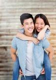 Glücklicher Mann, der piggyback der Frau gibt Lizenzfreie Stockfotos