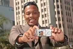 Glücklicher Mann, der sein Selbstportrait mit einer Tasche C nimmt Stockfoto