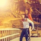 Glücklicher Mann, der seine Freundin auf der Rückseite an auf der Brücke O trägt Lizenzfreie Stockfotografie