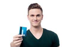 Glücklicher Mann, der seine Kreditkarte anbietet Lizenzfreies Stockfoto