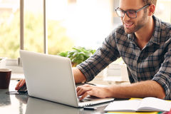 Glücklicher Mann, der an seinem Schreibtisch vom Haus sitzt und arbeitet Lizenzfreie Stockbilder