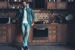 Glücklicher Mann, der seinen Kaffee während eines Bruches in der Küche genießt Stockfotos