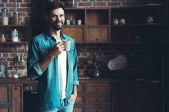 Glücklicher Mann, der seinen Kaffee während eines Bruches in der Küche genießt Lizenzfreie Stockbilder