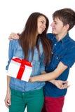 Glücklicher Mann, der seiner Freundin ein Geschenk gibt Glückliche junge schöne Paare lokalisiert auf einem weißen Hintergrund Stockfotos