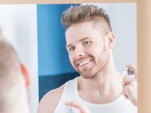 Glücklicher Mann, der sich parfümiert stockfotos