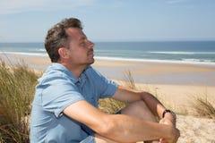 Glücklicher Mann, der tief auf dem Strand in den Ferien atmet Stockbild