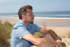 Glücklicher Mann, der tief auf dem Strand in den Ferien atmet stockbilder
