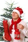 Glücklicher Mann in der Weihnachtskappe hält großen roten Sack Lizenzfreies Stockbild