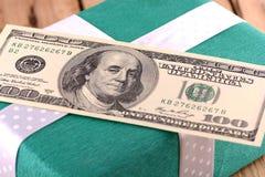Glücklicher Mann genießt an den Feiertagen in dem Meer amerikanisches Geld auf grüner Geschenkbox Stockbild