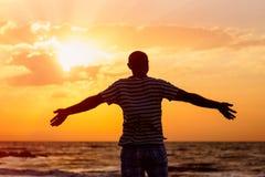 Glücklicher Mann hebt seine Arme oben gegen das Meer an Stockfoto