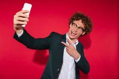 Glücklicher Mann im Eyewear, der selfie nimmt und Friedensgeste zeigt Stockfotografie