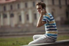 Glücklicher Mann im Freien. Unterhaltung auf dem Mobiltelefon Lizenzfreie Stockfotos