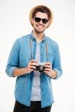 Glücklicher Mann im Hut und in der Sonnenbrille mit alter Fotokamera Stockfoto