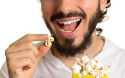 Glücklicher Mann isst Popcorn Schließen Sie oben vom Gesicht und von der Hand stockfotos