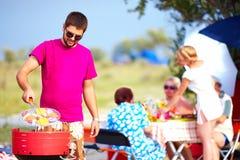 Glücklicher Mann kocht Gemüse auf dem Grill, Familienpicknick Stockbild