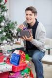 Glücklicher Mann mit den Geschenken, die durch Weihnachtsbaum sitzen Lizenzfreie Stockfotografie