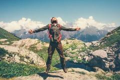 Glücklicher Mann mit den springenden Händen des Rucksacks angehoben lizenzfreie stockbilder