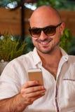 Glücklicher Mann mit der Sonnenbrille, die sein Telefon betrachtet Lizenzfreies Stockbild