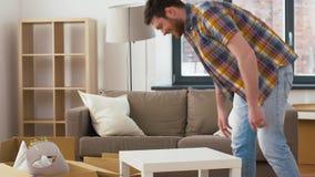 Glücklicher Mann mit der Tabelle und Kasten, die auf neues Haus sich bewegen stock footage