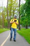 Glücklicher Mann mit einem Hut, einem gelben T-Shirt und einem Telefon geht in den Park Stockfotos