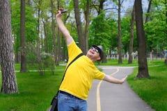 Glücklicher Mann mit einem Hut und einem gelben T-Shirt geht in den Park Stockfotos
