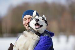 Glücklicher Mann mit einem Schlittenhund Stockfoto