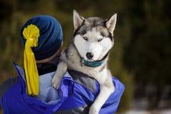 Glücklicher Mann mit einem Schlittenhund Stockbilder