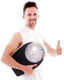 Glücklicher Mann mit einer Gewichtsskala Stockfotografie
