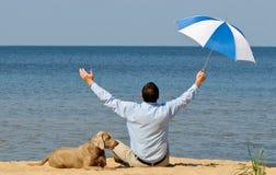 Glücklicher Mann mit Hund und Regenschirm lizenzfreies stockbild