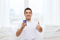 Glücklicher Mann mit Smartphone zu Hause Stockfotografie