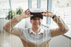 Glücklicher Mann mit VR-Kopfhörer, der hinter Schnittstellen steht Lizenzfreie Stockfotografie